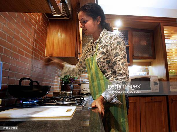 Former Indian model Divya Chauhan cooks a curry inside her kitchen in Bangalore 23 October 2006 She is one among many of a newly affluent generation...