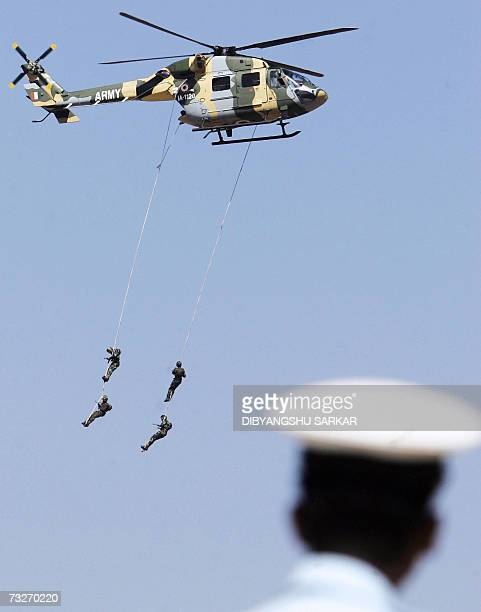 Indian Army commandos of the 202 Army Aviation Squadron hang from an Advance Light Helicopter as an Indian Air Force officer looks on during the...