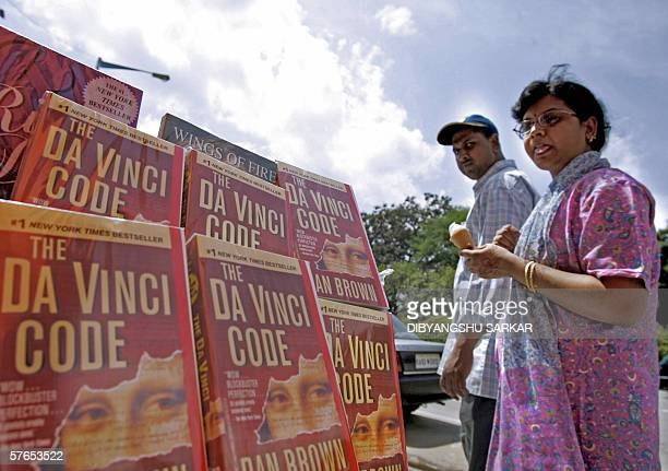 Indian women walk past a roadside book stall where copies of 'The Da Vinci Code' are displayed on sale in Bangalore 19 May 2006 India's film censors...