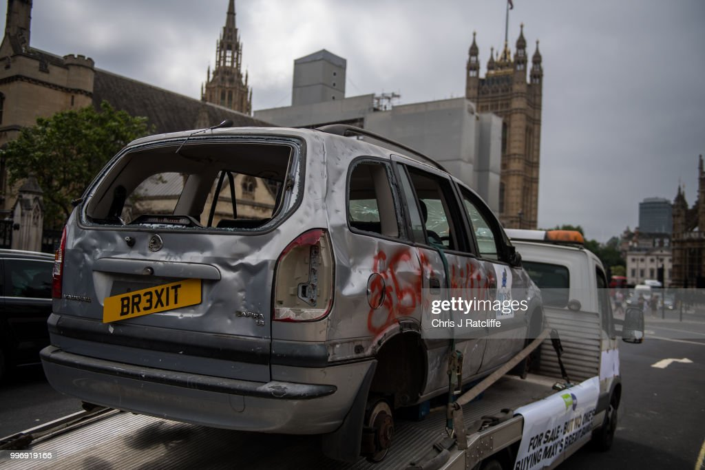 A banged up car decorated with a banner saying 'For sale - but no one's buying May's Brexit banger' is driven around Parliament Square on July 12, 2018 in London, England. The People's Vote Campaign organised the stunt on the day the Government are due to publish their White Paper on Brexit.