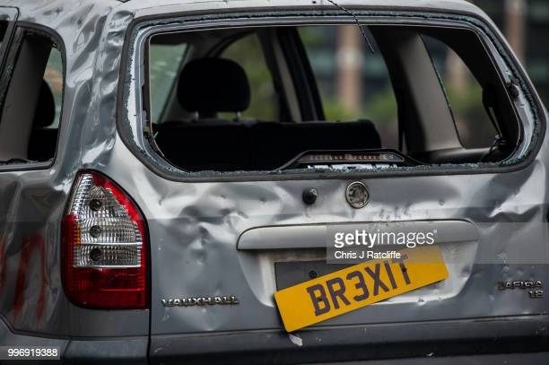 A banged up car decorated with a banner saying 'For sale but no one's buying May's Brexit banger' is driven around Parliament Square on July 12 2018...