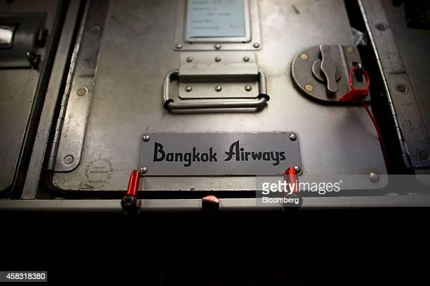 Bangkok Airways Co branding is displayed on a storage container inside an Airbus SAS A319 aircraft at Hong Kong International Airport in Hong Kong...