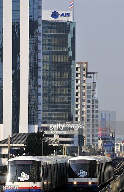 Bangkok Mass Transit System SkyTrains travel past the headquarters of Advanced Info Service Pcl located in Shinawatra Tower 2 in downtown Bangkok...