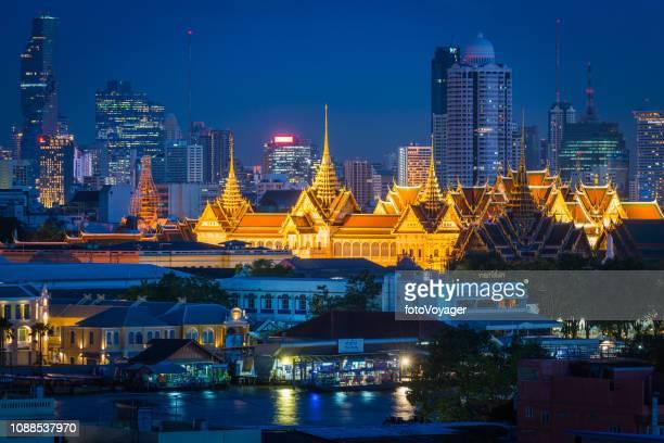 bangkok royal palace spotlit at night amid skyscraper cityscape thailand - grand palace - bangkok stock pictures, royalty-free photos & images