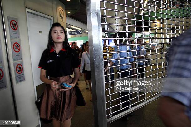 Bangkok Skytrain security officer closes shutters on a BTS station to temporarily close the station during an anti-coup demonstration at a shopping...