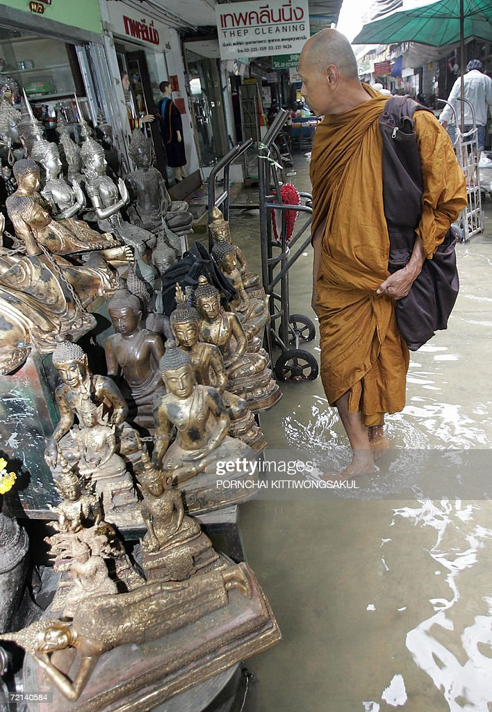 A buddhist monk walks in the flood as he visits amulet and buddha antique market in Bangkok, 11 October 2006. Severe flooding continued to wreak havoc across Thailand as the country's revered king granted permission for flood waters to be diverted onto his private land in a bid to spare Bangkok.