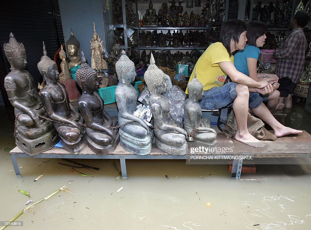 A couple sits next buddha statues during a flood at an amulet and buddha antique market in Bangkok, 11 October 2006. Severe flooding continued to wreak havoc across Thailand as the country's revered king granted permission for flood waters to be diverted onto his private land in a bid to spare Bangkok.