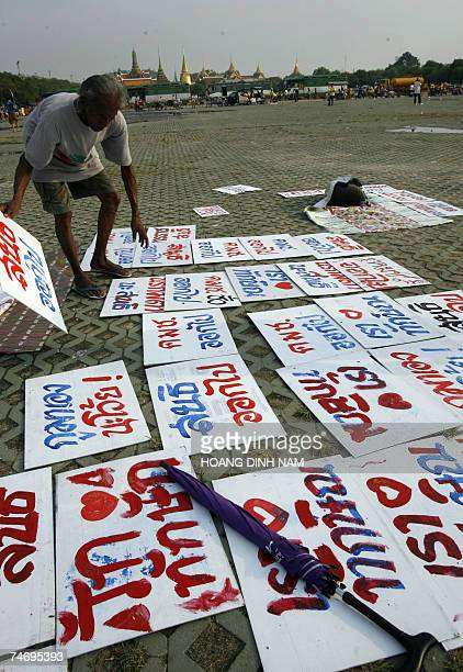 """Man places anti-coup posters with most of them reading """"military get out"""" on the ground after rain, at Sanam Luang square where the nighly..."""