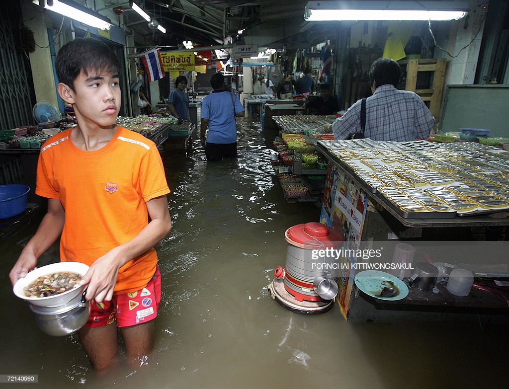 A teenager carries his food while walks in the flood at an amulet and buddha antique market in Bangkok, 11 October 2006. Severe flooding continued to wreak havoc across Thailand as the country's revered king granted permission for flood waters to be diverted onto his private land in a bid to spare Bangkok.