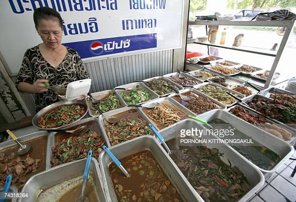 A Thai food vendor packs a food box for a client at a market in Bangkok 25 May 2007 The Bank of Thailand cut its key interest rate by a halfpoint to...