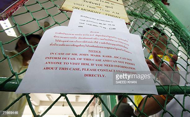 A Thai immigration offcer shuts the gate of the detention center next to a notice regarding information of arrested US teacher John Mark Karr at the...