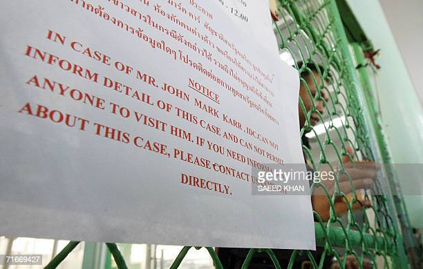 A Thai immigration offcer shuts the main gate of the detention center as a notice regarding information of arrested US teacher John Mark Karr hang on...