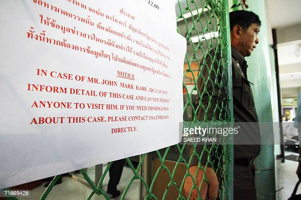A Thai immigration offcer stands next to a notice regarding information of arrested US teacher John Mark Karr at the main eneterence of the detention...