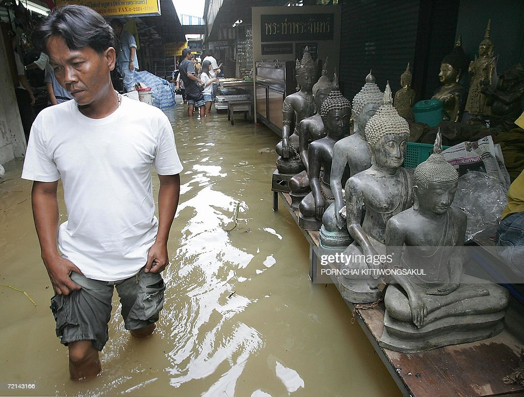 A Thai man walks in the flood as he visits a amulet and buddha antique market in Bangkok, 11 October 2006. Severe flooding continued to wreak havoc across Thailand as the country's revered king granted permission for flood waters to be diverted onto his private land in a bid to spare Bangkok.