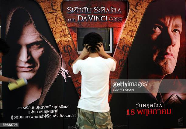 A Thai youth waits to watch a movie preview in front of an advertisement for the movie The Da Vinci Code outside a movie theater in Bangkok 17 May...