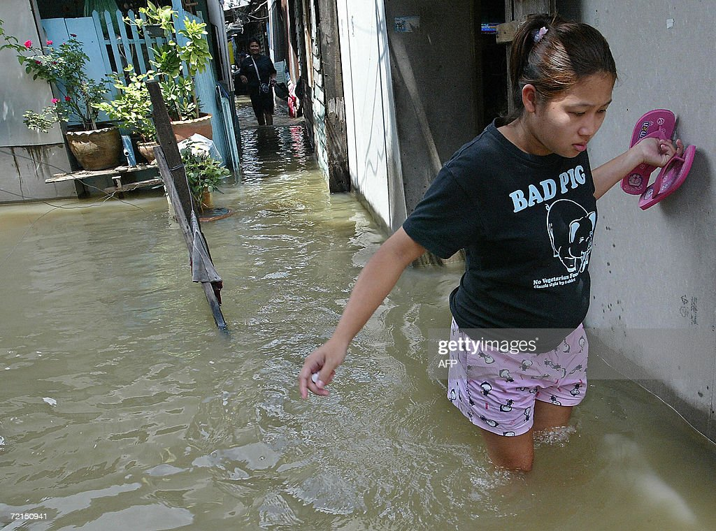 A woman holds her shoes while walking through flood waters in Bangkok, 12 October 2006. Thailand's rebounded tourism sector is being hard hit by severe flooding which lashed a number of tourism spots, with death toll rising to 44 people to date, experts said.