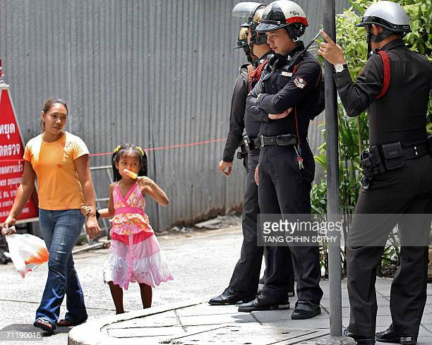 Woman with her daughter walk past Thai policemen standing guard outside a hotel where royal guests staying in Bangkok, 13 June 2006. Royalty from...