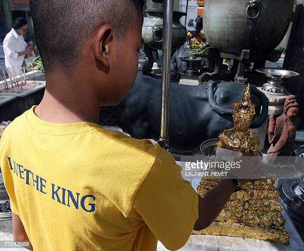 A youth wearing a yellow Tshirt places a gold leafe on a statue after offering a prayer inside the Grand Place in honor of Thai King Bhumibol...