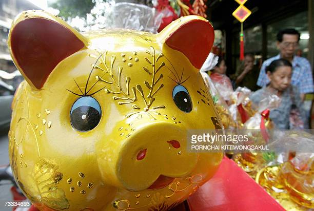 An elderly couple walk past a mascot of a pig prior to Lunar New Year celebrations in the Chinatown section of Bangkok 15 February 2007 The lunar...