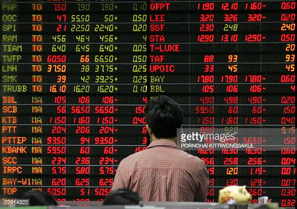 An investor talks on his mobile phone while looking at an electronic shares display prices at the Stock Exchange in Bangkok 03 January 2007 Thai...