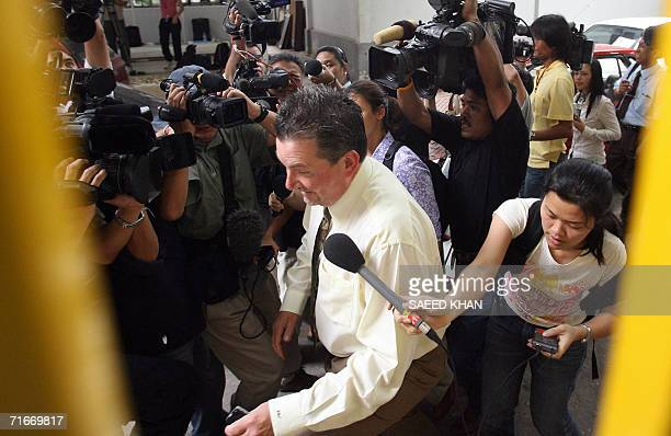 An unidentified US official from the US embassy in Bangkok tries to avoid media on his way out from the detention center where US teacher John Mark...