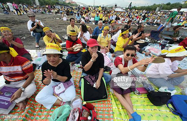 Anti-coup protestors clap while listening to speeches of their leaders during a demonstration at the Sanam Luang in front of the famous Grand Palace...