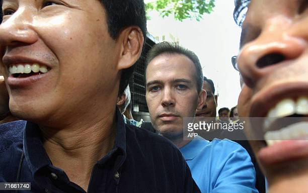 Cheerful Thai security officers laugh while escorting US teacher John Mark Karr at the Thai Immigration Department in Bangkok 17 August 2006 Karr who...