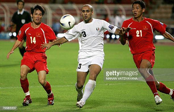 Iraqi footballer Bassim Abbas vies for the ball with Vietnamese opponents Le Tan Tai and Nguyen Anh Duc during the Asian Football Cup 2007 first...
