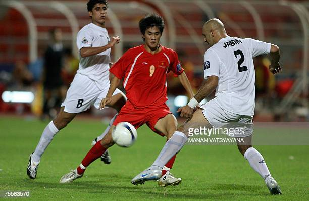 Iraqi footballer Jassim Mohammed vies for the ball with Vietnamese Le Cong Vinh during the Asian Football Cup 2007 first quarterfinal match between...