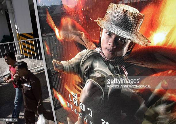 Pedestrians walk past a poster of Thai action film 'Kon Fire Bin' displayed in Bangkok 10 December 2006 Thailand is aiming for another blockbuster in...