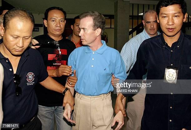 Thai police officials escort away US teacher John Mark Karr at the Thai Immigration Department in Bangkok 17 August 2006 Police said 17 August that...