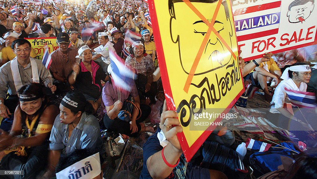Thai protesters hold placards during a protest rally against Thai
