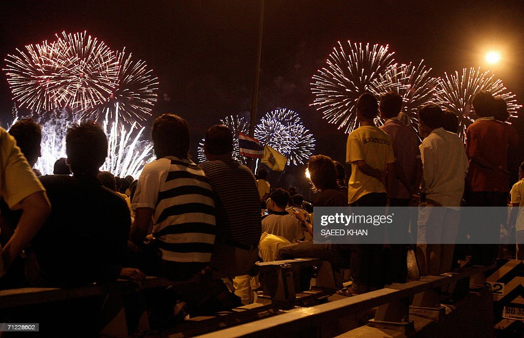 Thai well-wishers enjoy fireworks to mark the 60th anniversary on the throne of revered King Bhumibol Adulyadej in Bangkok, 17 June 2006. Royalty from 25 countries came to Thailand last week for a Grand Palace banquet for the 78-year-old king and other glittering events, including a rare procession of 52 elaborately carved royal barges on the Chao Praya River. AFP PHOTO / Saeed KHAN