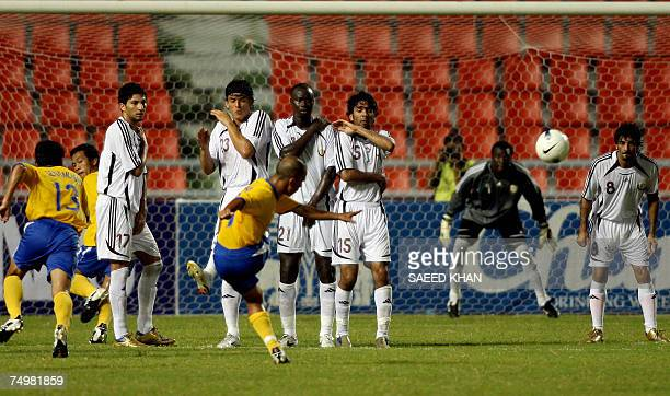 Thailand footballer Therdsak Chaiman threads a freekick past a wall of Qatar players during a friendly match at The Ratchamangla Stadium in Bangkok...
