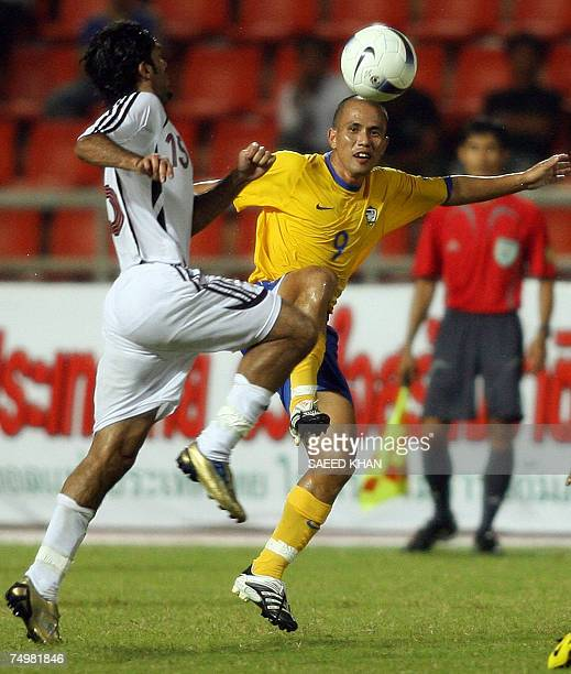 Thailand footballer Therdsak Chaiman vies with Qatar defender Talal Ali H Albloushi for the ball during a friendly match at the Ratchamangla Stadium...