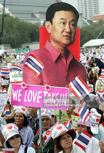 Thaksin supporters hold his portrait and wave Thai national flags during attend rally support Thai Prime Minister Thaksin Shinawatra at Sanam Luang...