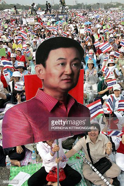 Thaksin supporters hold his portrait as they wave Thai national flags during attend rally support Thai Prime Minister Thaksin Shinawatra at Sanam...