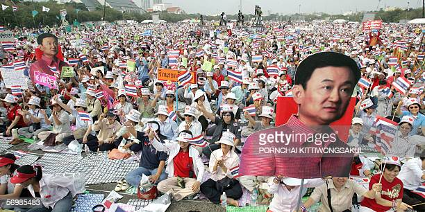 Thousands of Thaksin supporters wave Thai national flags during attend rally support Thai Prime Minister Thaksin Shinawatra at Sanam Luang in...