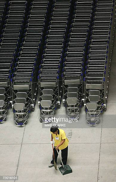 TO GO WITH Thailandaviationairporttourismsexsched A cleaner works in front of rows of luggage trolleys at the new Suvarnabhumi airport near Bangkok...