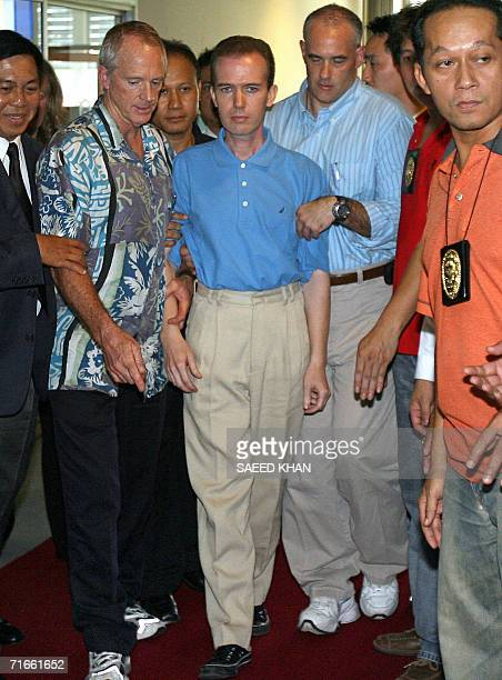 US officials escort US teacher John Mark Karr at the Thai Immigration Department in Bangkok 17 August 2006 John Mark was arrested in Thailand over...