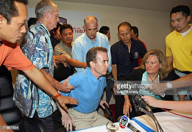 US officials take away US teacher John Mark Karr in the middle of a press conference at the Thai Immigration Department in Bangkok 17 August 2006...
