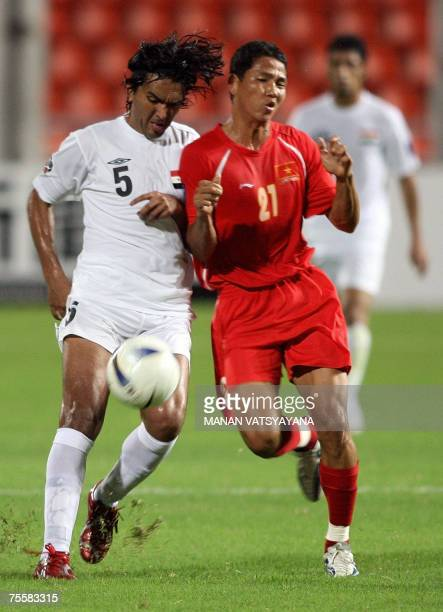 Vietnamese footballer Nguyen Anh Duc is tackled by Iraqi Nashat Akram during the Asian Football Cup 2007 first quarterfinal match between Iraq and...
