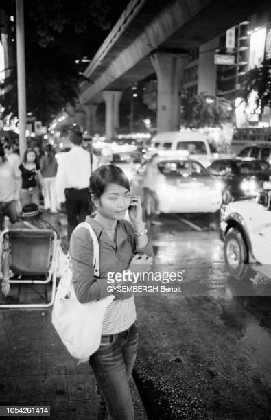 Bangkok, Thaïlande, septembre-octobre 2005 --- Jeune femme téléphonant dans la rue, de nuit.