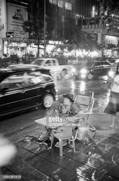 Bangkok Thaïlande septembreoctobre 2005 Une femme assise à une table seule au milieu d'un trottoir