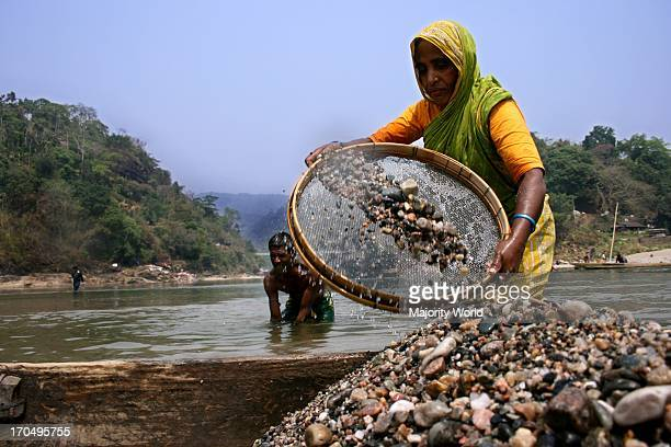 A woman is digging stones from Jaflong lake in Sylhet district in early morning 2007