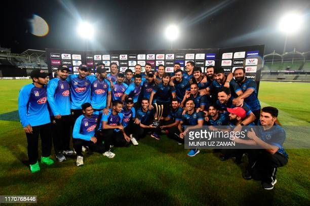 Bangladesh and Afghanistan cricketers pose for a photo with the tournament trophy after the match was abandoned for rainfall during the final...
