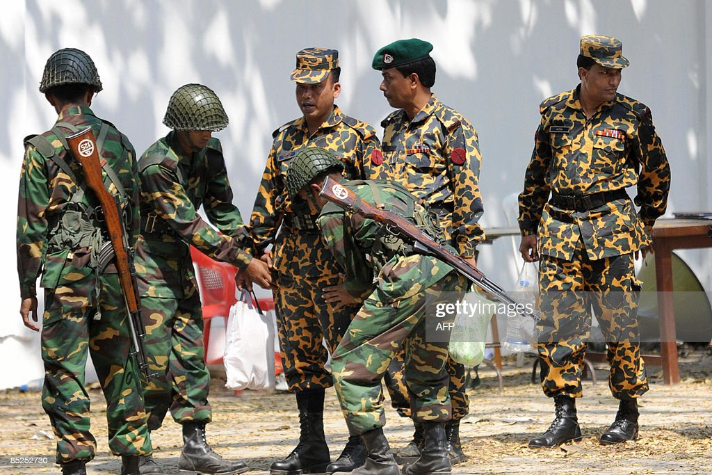 Bangladesh Army soldiers (2nd L, 3rd R) search a Bangladeshi border soldier (C) at the entrance to the Bangladesh Rifles headquarters in Dhaka on March 3, 2009. The Bangladesh military launched its own probe into a savage mutiny by troops against their officers, raising fears of a power struggle between the army and the newly elected civilian government. Prime Minister Sheikh Hasina, who won polls in December that ended two years of army rule in the country, had already set up an investigation into the revolt in which 74 people died. AFP PHOTO/Munir uz ZAMAN