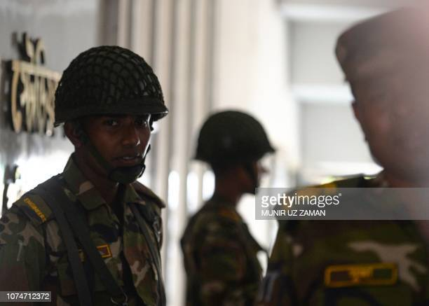 Bangladesh Army soldiers stand guard at a temporary base set up in Dhaka on December 24 as the security forces begin general election duties across...