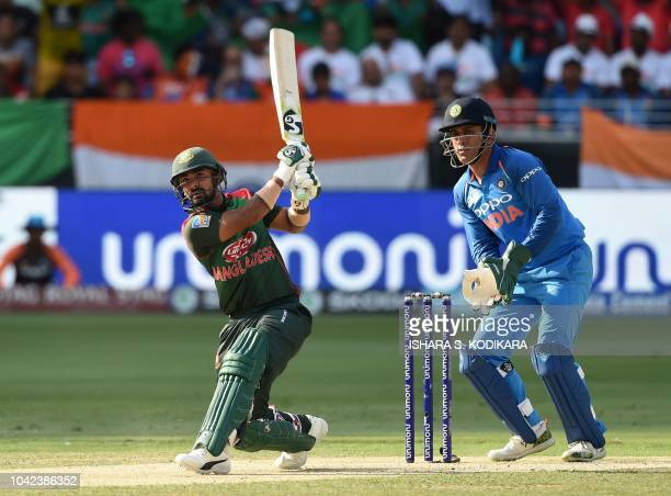Bangladesh batsman Liton Das plays a shot as Indian wicketkeeper Mahendra Singh Dhoni looks on during the start of the final one day international...
