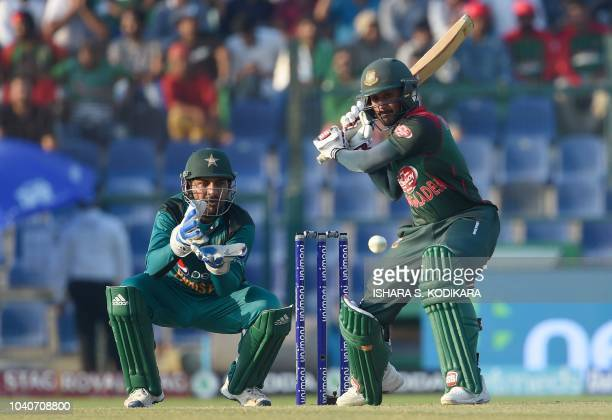 Bangladesh batsman Mohammad Mithun plays a shot as Pakistan captain Sarfraz Ahmed looks on during the one day international Asia Cup cricket match...
